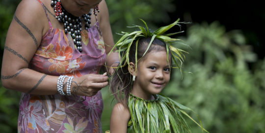 Polynesian woman making traditional costum on her daughter